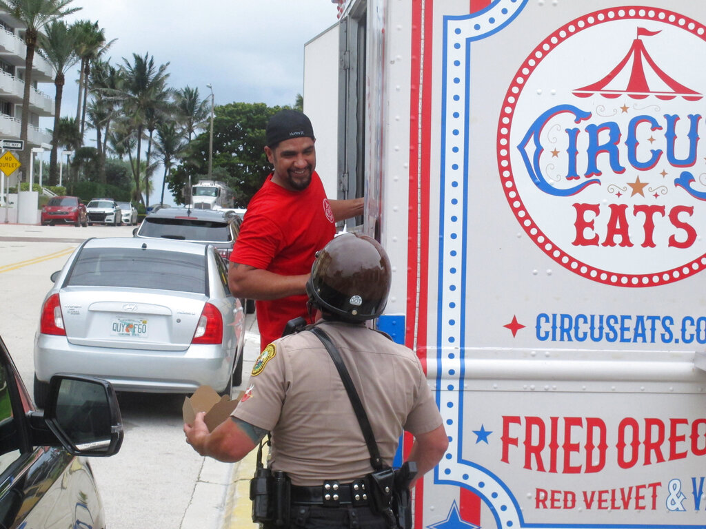 Robert Martinez talks with a law enforcement officer after handing him a hot meal from his food truck in Surfside, Fla., Tuesday, June 29, 2021. A small army of volunteers mobilized to deliver bottled water and energy drinks, chicken tenders and pizzas to law enforcement and emergency crews working long shifts after the deadly collapse of a condominium tower in the city, near Miami. (AP Photo/Russ Bynum)