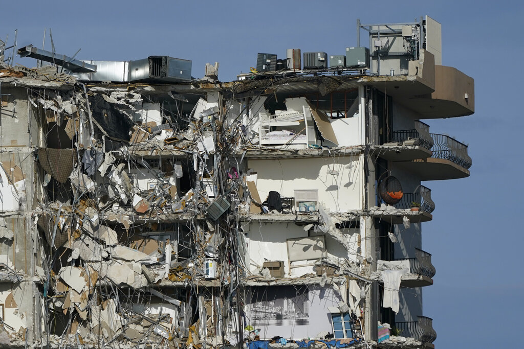 Furniture and household items are perched in the remains of destroyed apartments, in the still standing section of the Champlain Towers South condo building on Thursday, July 1, 2021, in Surfside, Fla. Scores of people remain missing one week after the building partially collapsed.(AP Photo/Mark Humphrey)