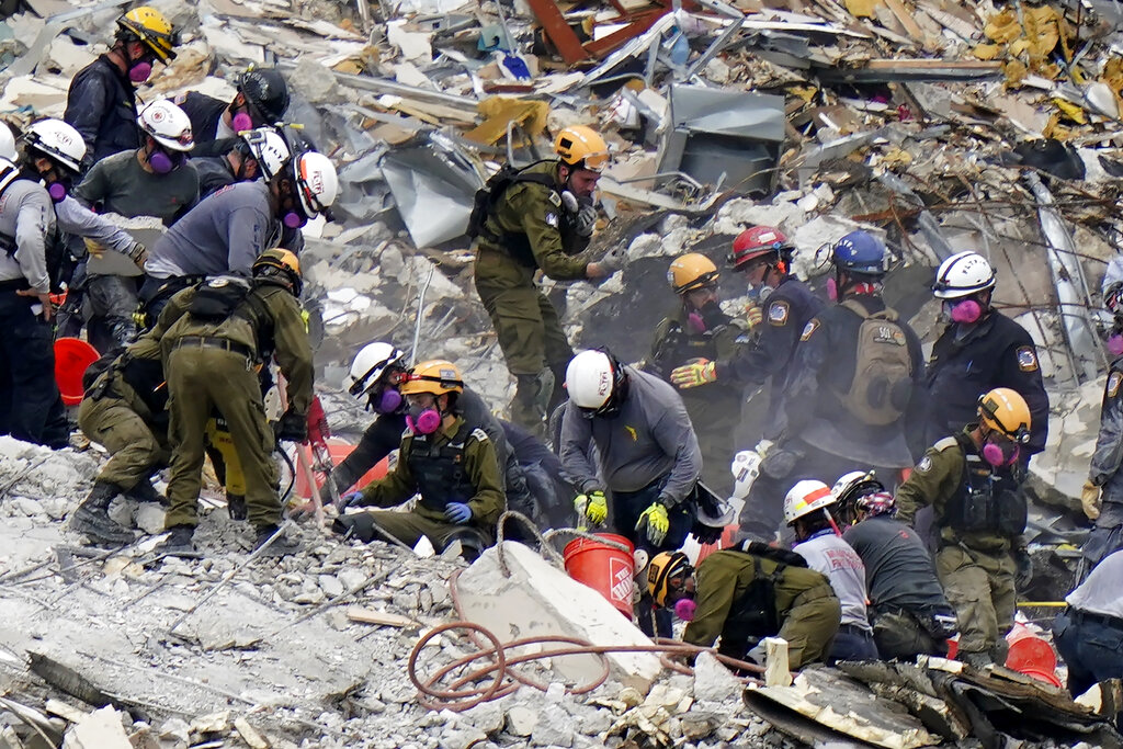 """Crews from the United States and Israel work in the rubble Champlain Towers South condo, Tuesday, June 29, 2021, in Surfside, Fla. The Israeli search and rescue team that arrived in South Florida shortly after the Champlain Towers South collapsed last month is heading home after an emotional sendoff in Surfside. The team planned to leave Florida on Sunday, July 11. During a brief Saturday evening ceremony, Miami-Dade Mayor Daniella Levine Cava thanked the battalion for their """"unrelenting dedication."""" (AP Photo/Lynne Sladky, File)"""