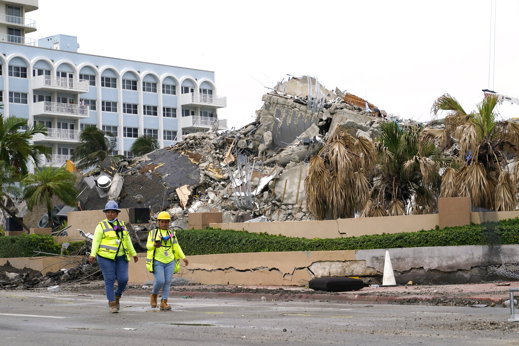 Workers walk past the collapsed Champlain Towers South condominium building, Tuesday, July 6, 2021, in Surfside, Fla. (AP Photo/Lynne Sladky)