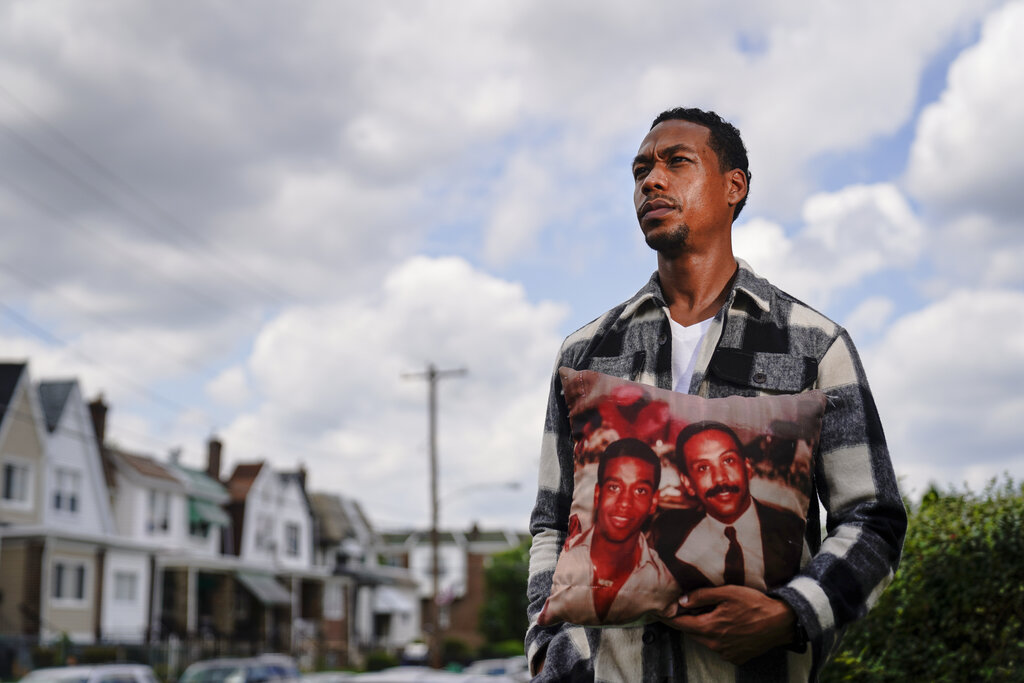 Brett Roman Williams poses for a photograph while holding a pillow with a photo of his father, Donald Williams, lower right, and brother Derrick Williams who both were killed by gunfire 20 years apart, in Philadelphia. (AP Photo/Matt Rourke)