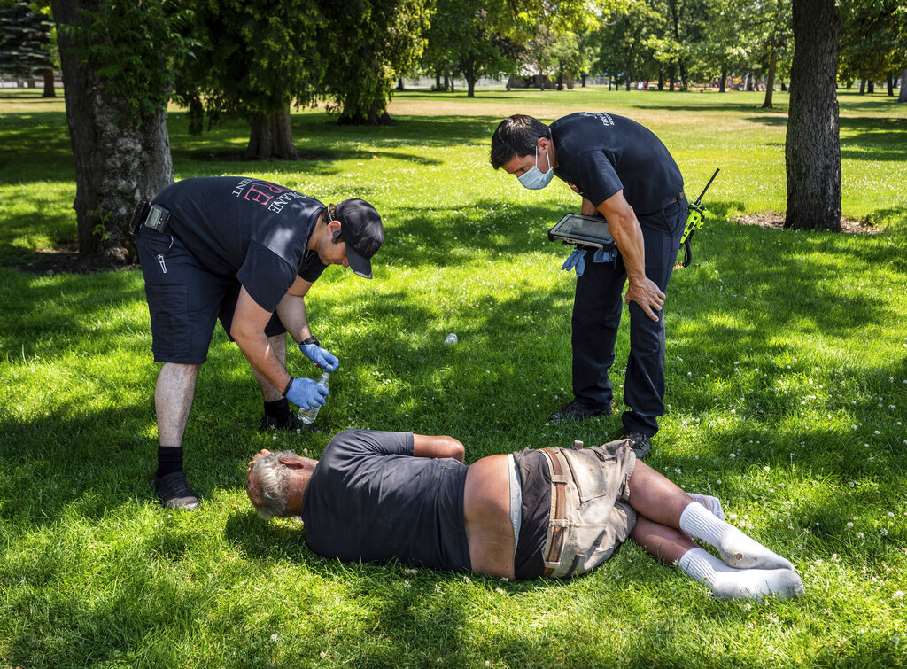 With the temperature well over 100 degrees, Spokane, Wash., firefighter Sean Condon, left and Lt. Gabe Mills, assigned to the Alternative Response Unit of of Station 1, check on the welfare of a man in Mission Park in Spokane, Washington. The special fire unit, which responds to low priority calls, has been kept busy during this week's heatwave. (Colin Mulvany/The Spokesman-Review via AP)
