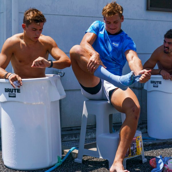 Argentina's Santiago Mare, center, takes off his sock as Marcos Moneta, left, and fellow teammates soak in ice baths following men's rugby sevens team practice in the midday heat at the Tokyo 2020 Olympics, in Tokyo, Friday, July 23, 2021. (AP Photo/David Goldman)